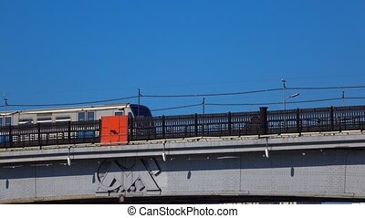 Moscow metro train with city emblem passing river bridge...