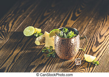 Moscow mule alcoholic cocktail in copper mug with crushed ice, mint and lemon over minton dark wooden table with amazing backlight, copy space