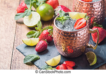Moscow mule cocktail in copper cup with lime, strawberry, ...