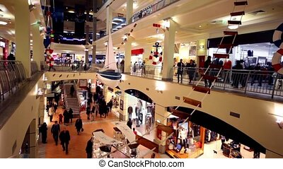 Customers walk along boutiques on multiple floors trade center Atrium at Kurskaya
