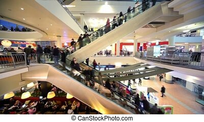 Many people move on escalators in multiple floors shopping center Atrium