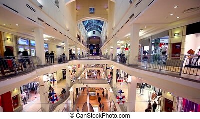 People walk along boutiques on multiple floors shopping center Atrium