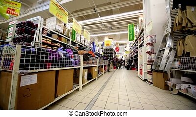 Few people walk among shelves with goods in hypermarket...
