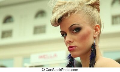 Blonde with fanciful hairdo and plum earring at XVII...