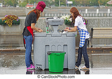 Moscow, Russia - August 18, 2012: Young women washing dishes in rainy weather in Gorky Park in Moscow