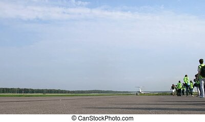 Spotters gather near runway with moving planes on Domodedovo...