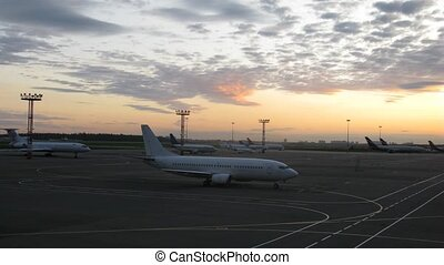 Planes stands on take-off field on sunset in twilight -...