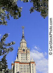 Moscow State University against sky background with branch of flowering trees