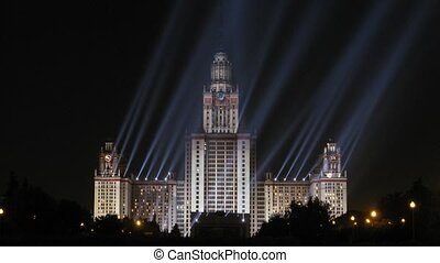 Moscow State University is shone at night by projectors,...