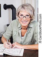 mosolygós, öregedő woman, doing crossword, rejtvény