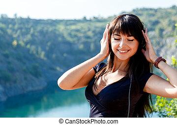 mosolygós, barna nő, leány, noha, hosszú szőr, kihallgatás, a, zene, képben látható, a, háttér, közül, egy, hegy, folyó