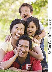 mosolygós, család, fekvő, szabadban