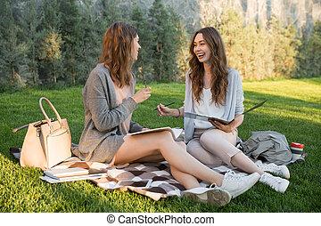 mosolygós, fiatal, 2 women, ülés, szabadban, dísztér, írás, hangjegy.