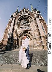 mosolygós, newlywed, összekapcsol táncol, és, ölelgetés, közel, öreg, gót, keresztény, székesegyház