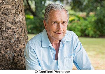 mosolygós, nyugdíjas, bábu ül, képben látható, fatörzs