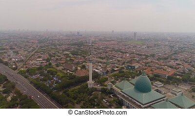 aerial view cityscape city Surabaya with mosque Al Akbar, highway, skyscrapers, buildings and houses. mosque in Indonesia Al Akbar in Surabaya, Indonesia. beautiful mosque with minarets on island Java Indonesia.