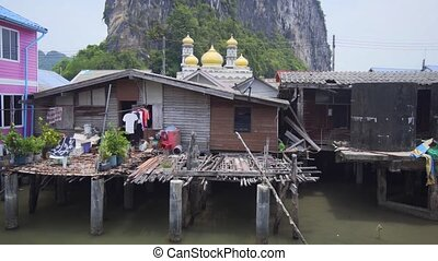 Gold-domed mosque and dramatic limstone formation presiding over these houses on stilts at the remote Panyee Island, in Thailand. Ultra HD stock footage
