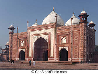 White marble decorations on red sandstone and tipped domes against blue skies.