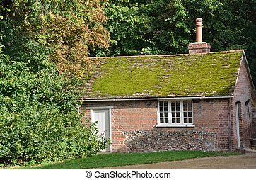 Moss Roofed red brick cottage