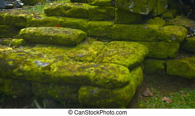 Mossy heap of stone rubble fromancient rock walls of temple...