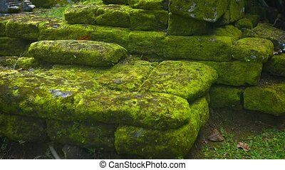 Mossy heap of stone rubble from the ancient rock walls of a temple ruins. Video 4k