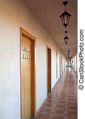 Motel corridor with many wooden closed doors