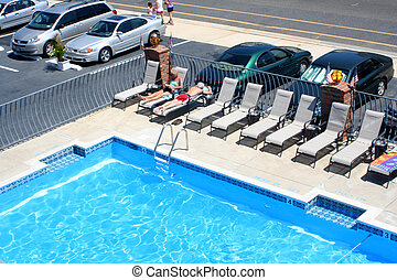 View of the corner of a motel pool, as well as the surrounding seating area.