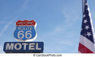 Motel retro sign on historic route 66 famous travel destination, vintage symbol of road trip in USA. Iconic lodging signboard in Arizona desert. Old-fashioned neon signage. National state flag waving