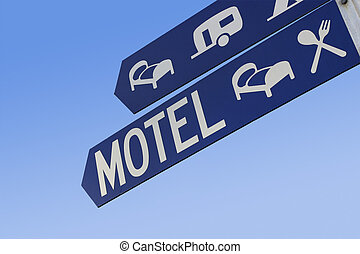 Motel sign - A blue street sign shows the way to...