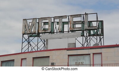 Big sign on top of cheap motel. Pigeons landing.