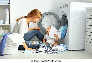 mother a housewife with a baby fold clothes into the washing...