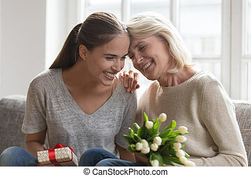 Mother adult daughter sitting on chair with gift and flowers