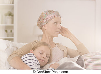 Mother after chemotherapy embracing child