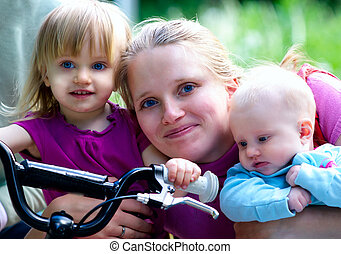 Happy mother with 2 same age daughters. One 2 years old and another 3 month old.