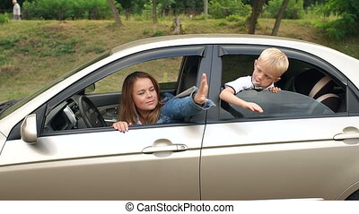 Mother and a child look out of the car window and slap each other on the arm.