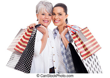mother and adult daughter carrying shopping bags - cheerful...