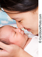 Mother and baby - An asian mother kissing her sleeping baby...