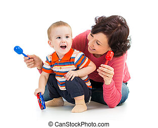 Mother and baby boy having fun with musical toys. Isolated...