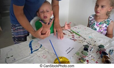 Mother and baby boy making palm print with watercolor on paper. Gimbal motion