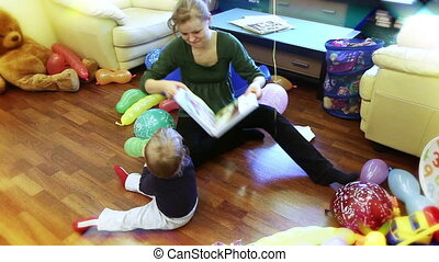 Mother and baby boy playing and reading stories