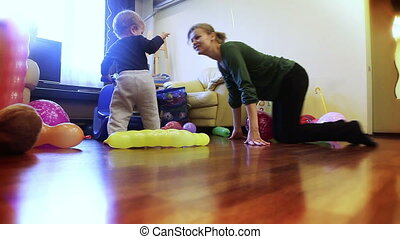 Mother and baby boy playing, ridding a toy horse