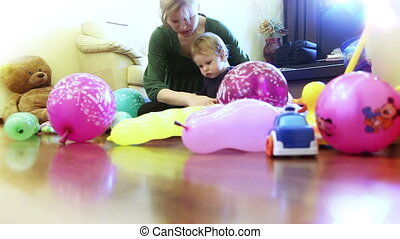 Mother and baby boy playing, surrounded by toys