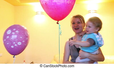 Mother and Baby Boy playing with colorful balloons