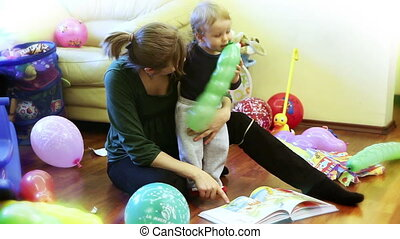 Mother and baby boy reading stories, surrounded with toys