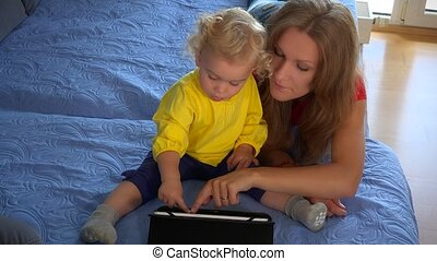 mother and baby child playing with tablet computer on couch at home.