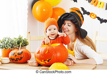 mother and baby cut  pumpkin for Halloween in kitchen
