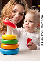 Mother and baby daughter building pyramid - Young mother and...