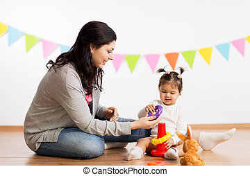 mother and baby daughter playing with pyramid toy