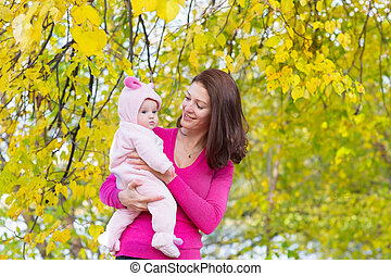 Mother and baby daughter standing under a yellow tree on a sunny autumn day