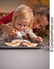 Mother and baby decorating homemade christmas cookies with ...